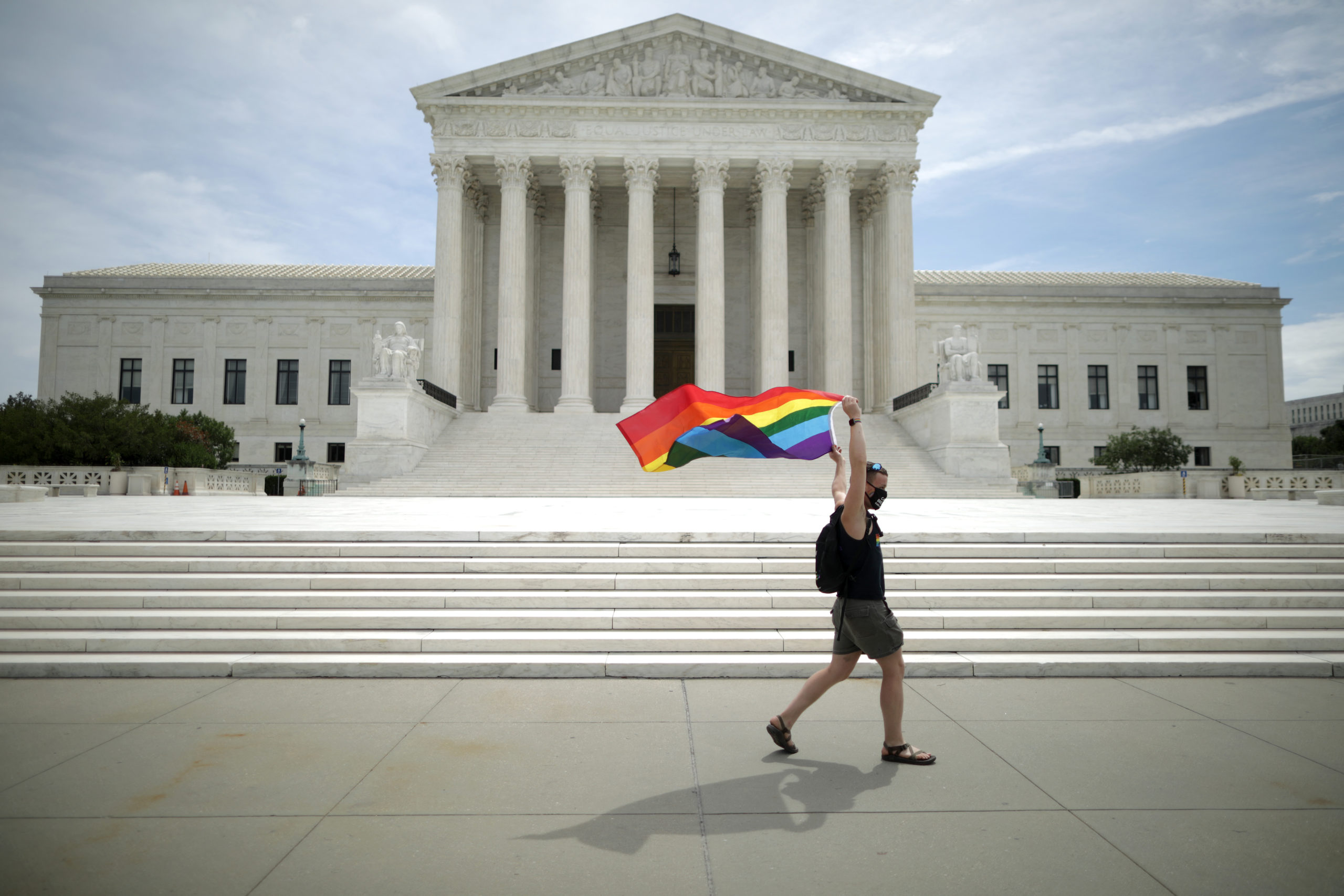 person carrying pride flag in front of government building
