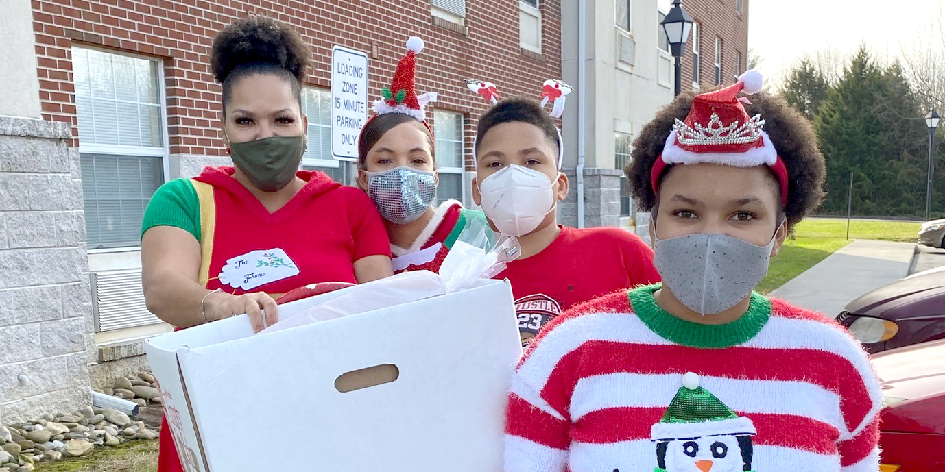 A mom and her children wearing festive outfits and masks deliver food to residents